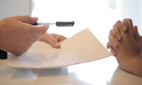 A man's hands offering sa pen to another set of hands implying they should sign a document